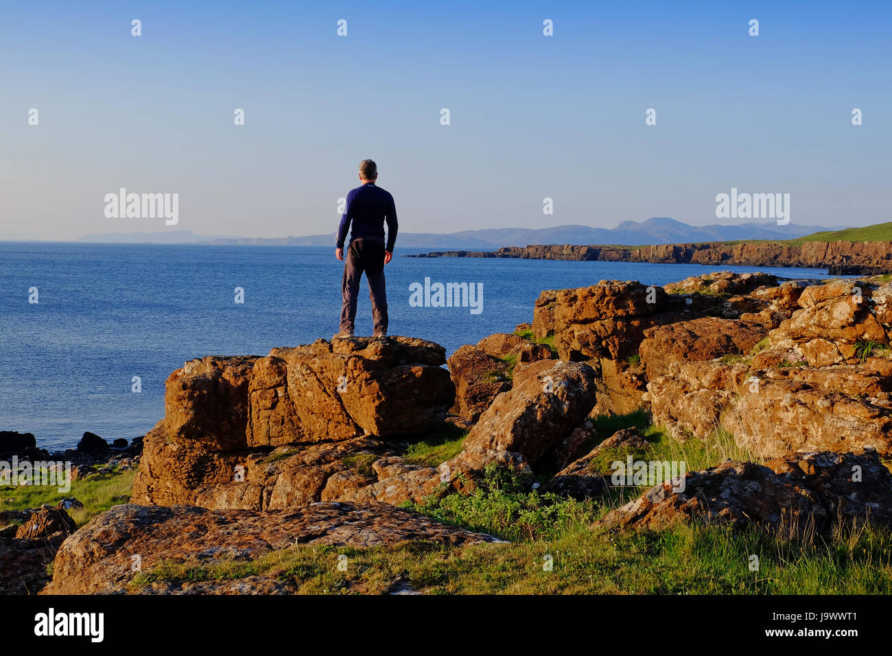 Man standing on rocks looking out to sea, Mull, Scotland - Stock Image