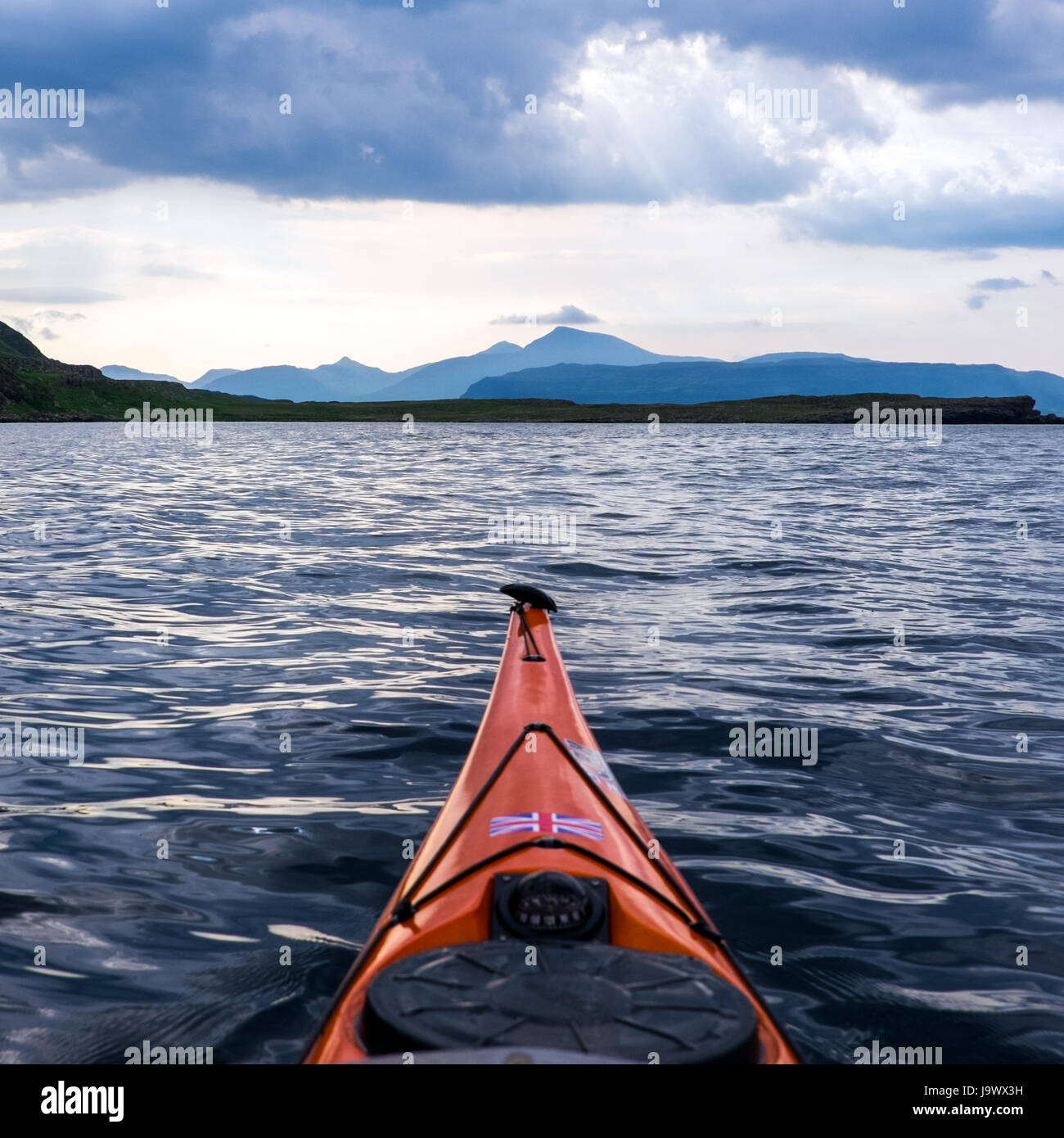 sea kayaking near Ulva,Mull, on Scotalnd's West coast with Ben More in the distance - Stock Image