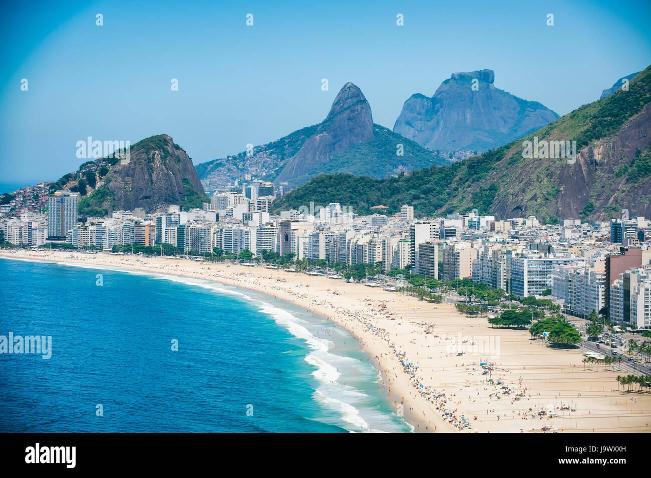 Bright scenic view of the Rio de Janeiro, Brazil skyline overlooking the shore of Copacabana Beach and dramatic - Stock Image