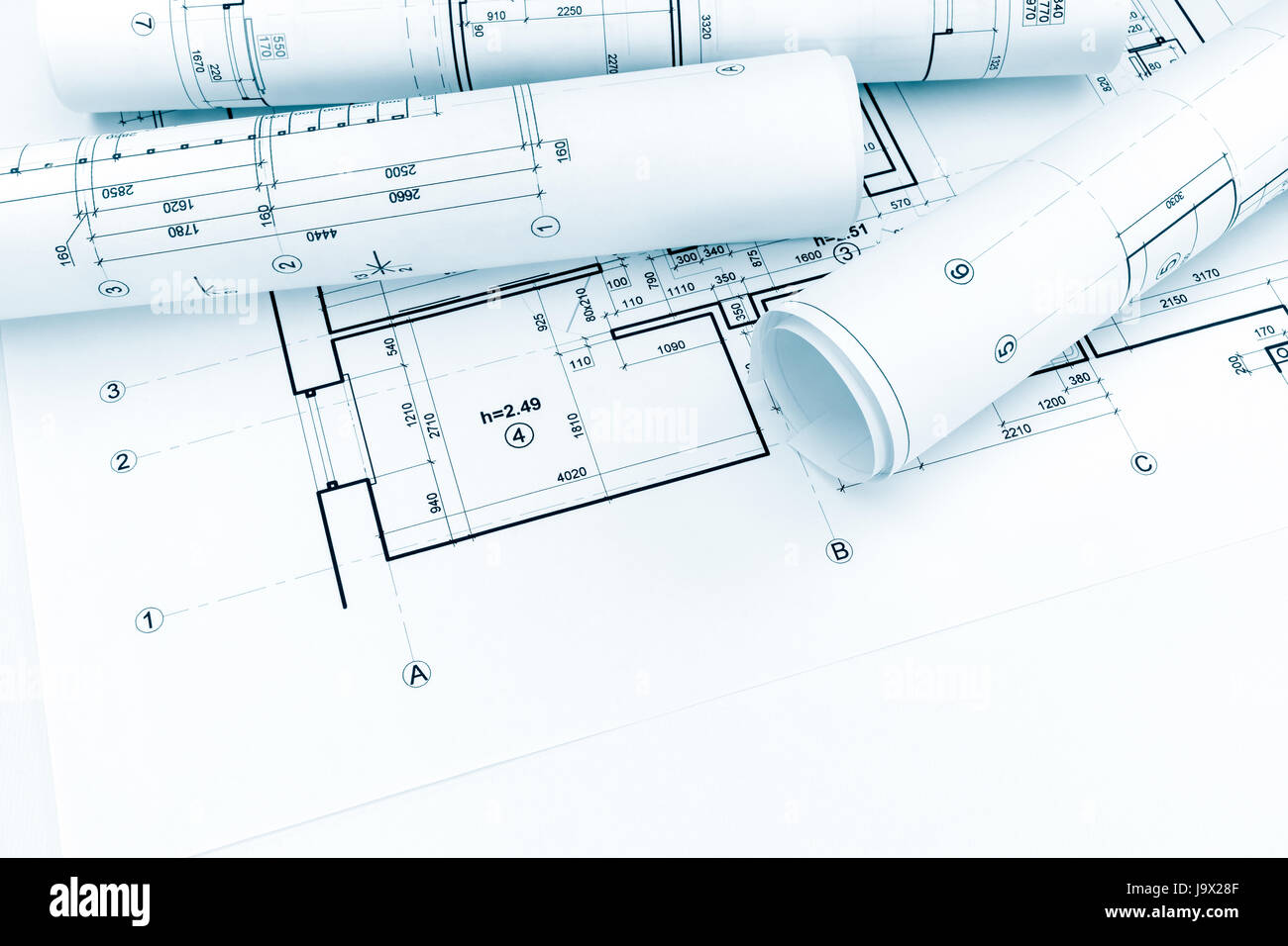 Rolled Architectural Plans And Technical Drawings On House Blueprint  Background