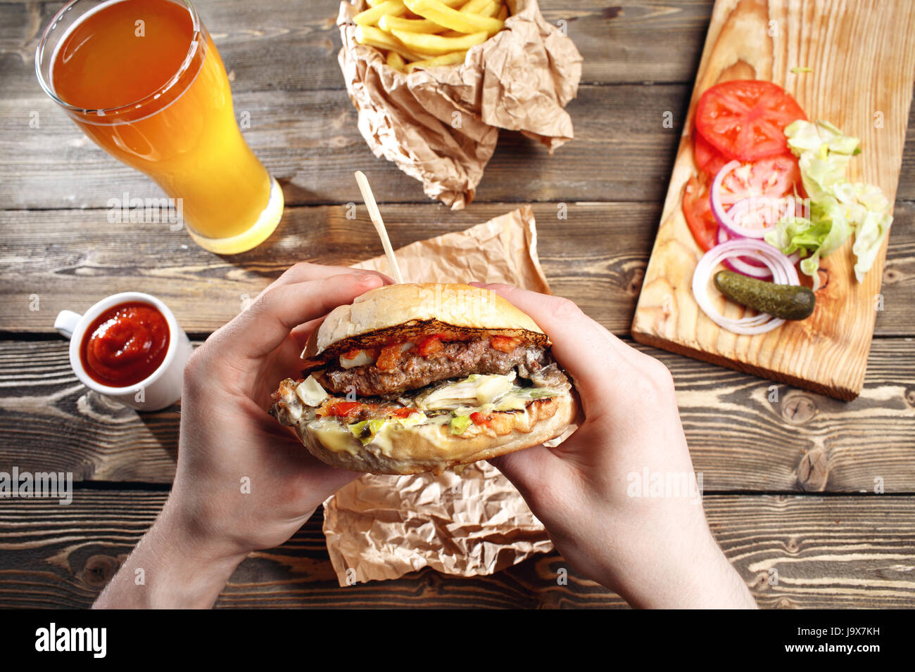 Hands holding fresh delicious burgers with french fries, sauce and beer on the wooden table top view. Stock Photo