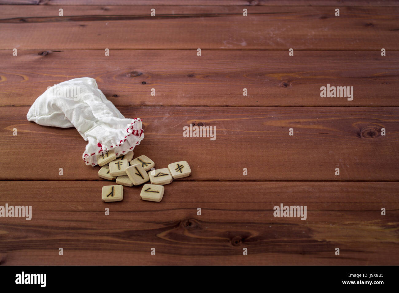 Bag with Slavic runes on a wooden background. Close-up. - Stock Image