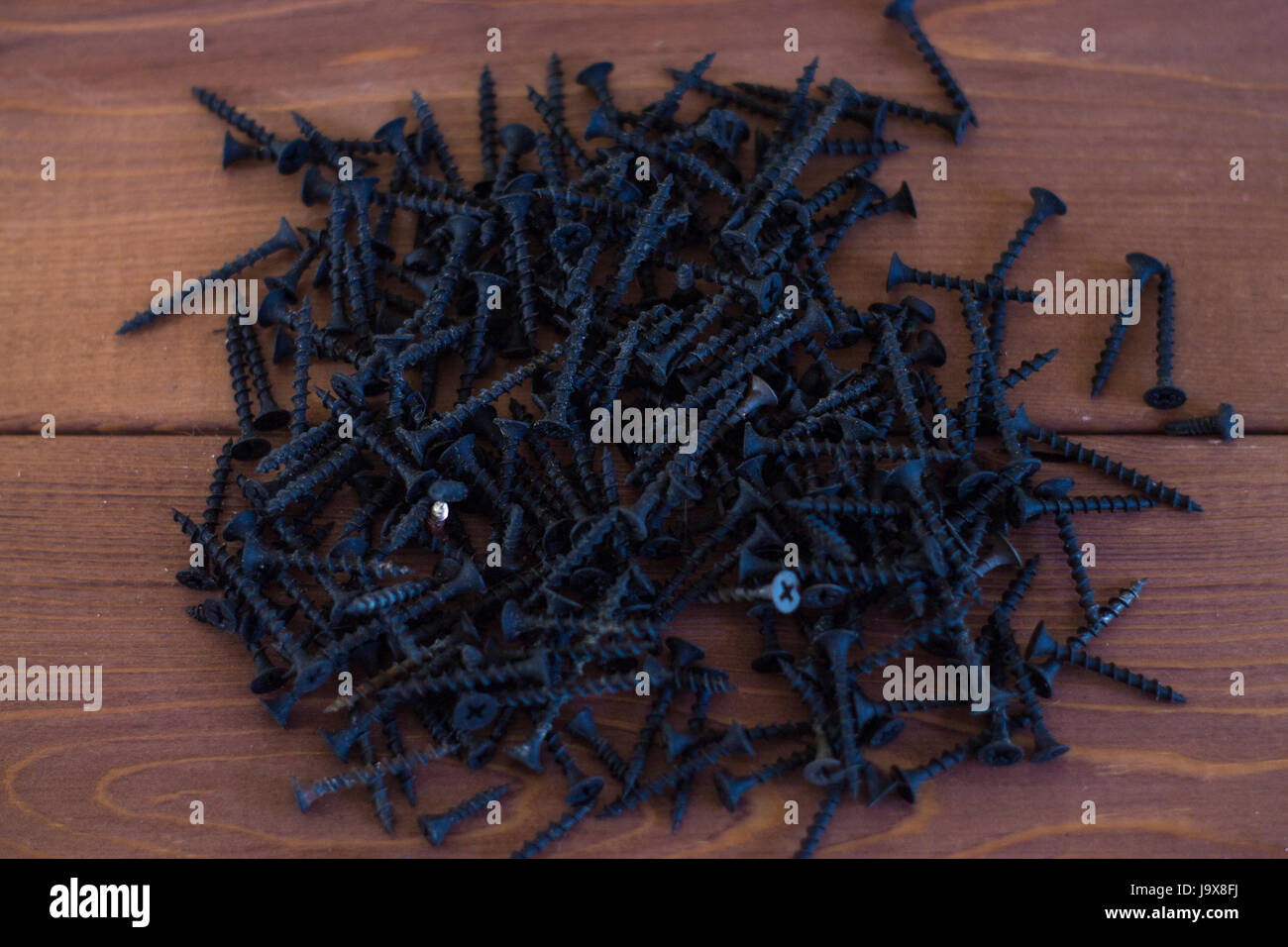 Black self-tapping screws on a wooden background. - Stock Image