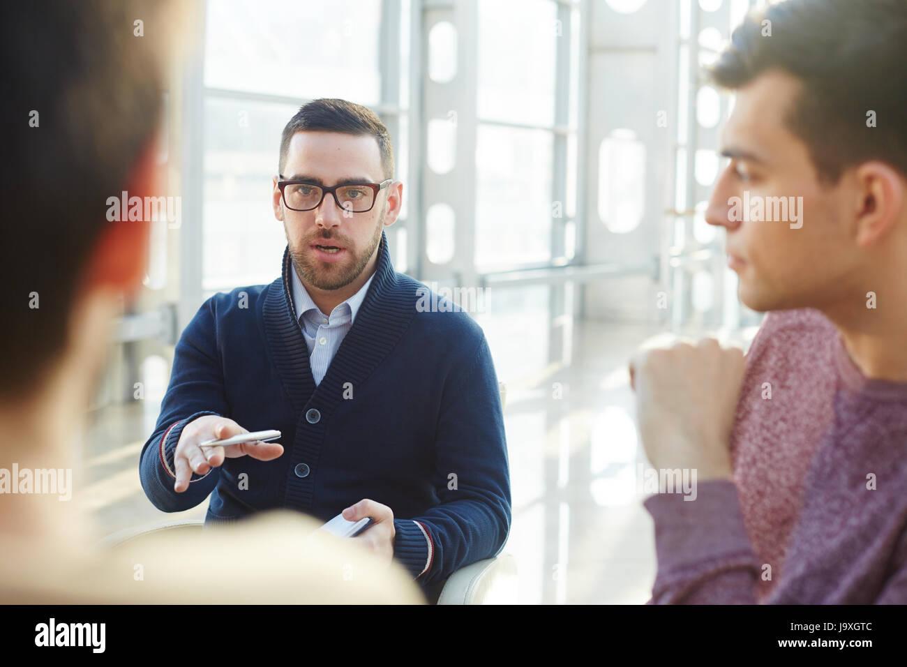 Confident ceo explaining something to one of employees - Stock Image