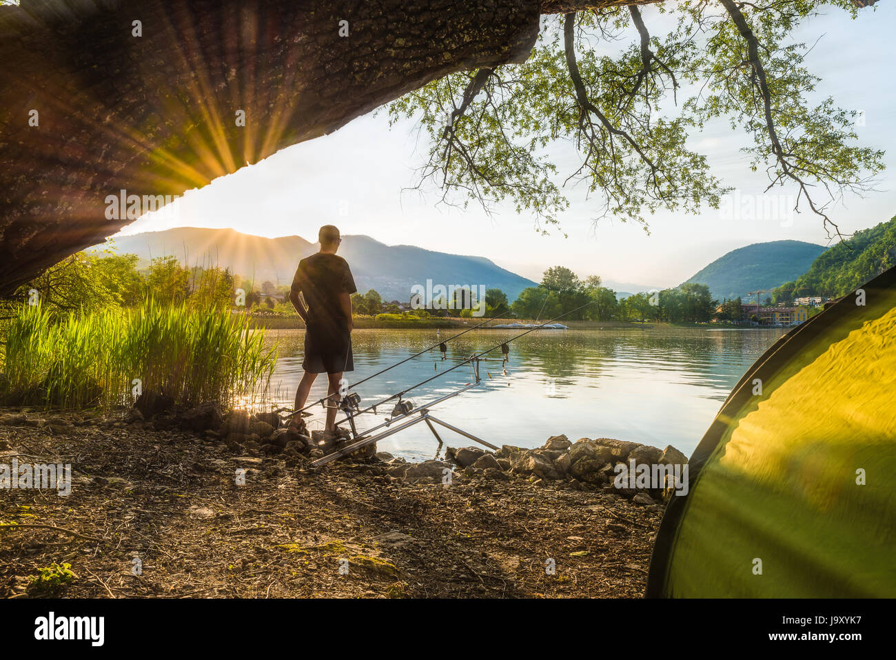 Fishing adventures, carp fishing. Angler, at sunset, is fishing with carpfishing technique. Camping on the shore - Stock Image