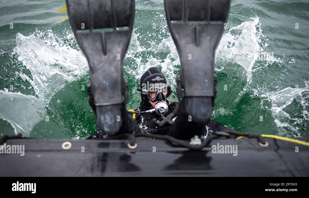 A U.S. sailor dives off a rigid-hull inflatable boat during a mine countermeasure drill for exercise Open Spirit - Stock Image