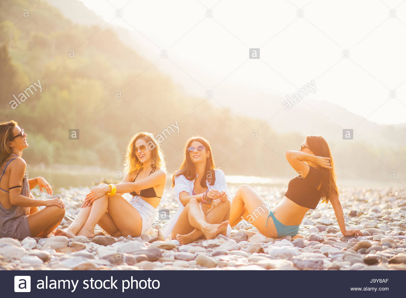 Young women enjoy in summer sunset on river beach - Stock Image