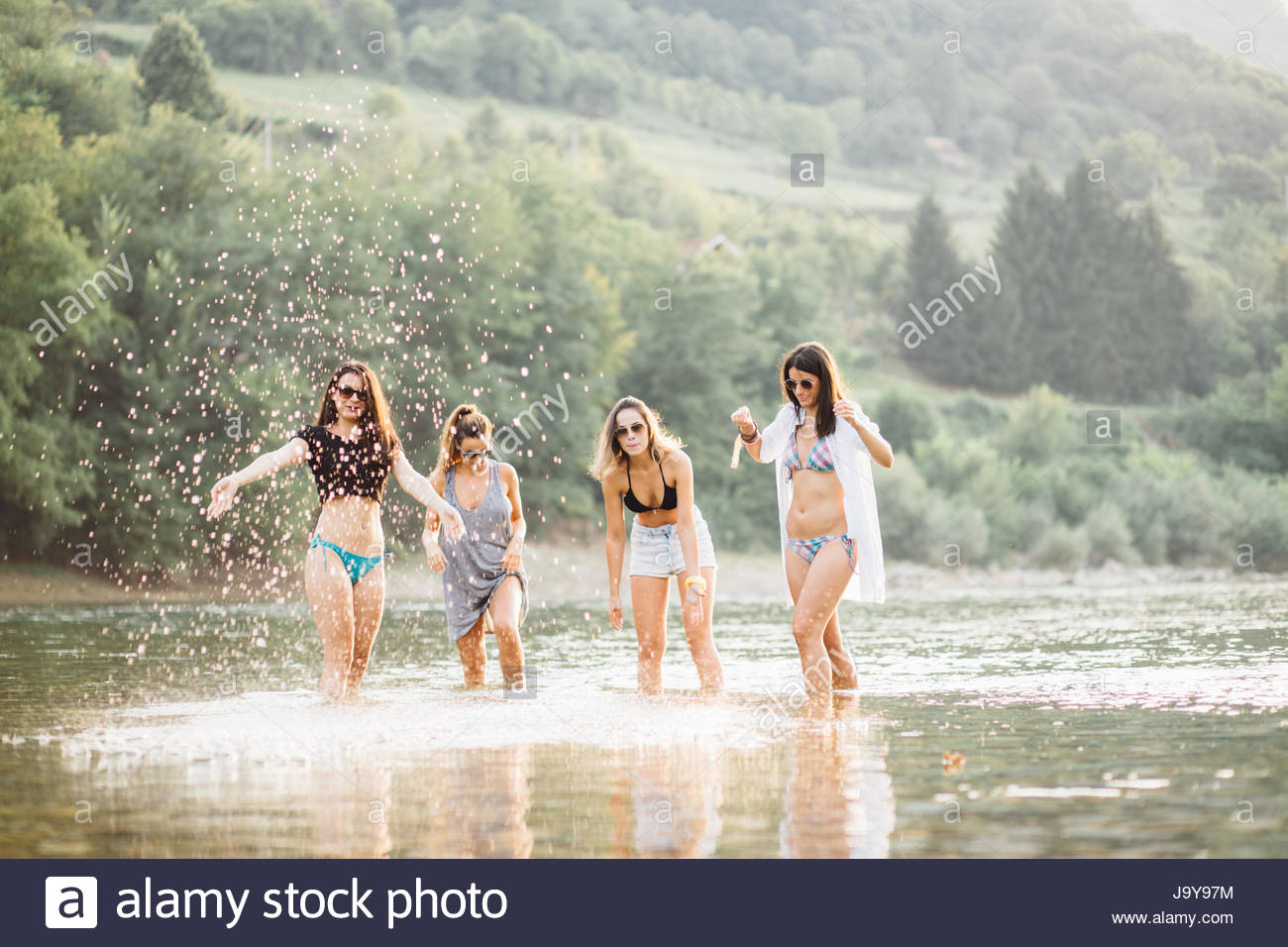 Young women on beach in summer sunset having good time - Stock Image