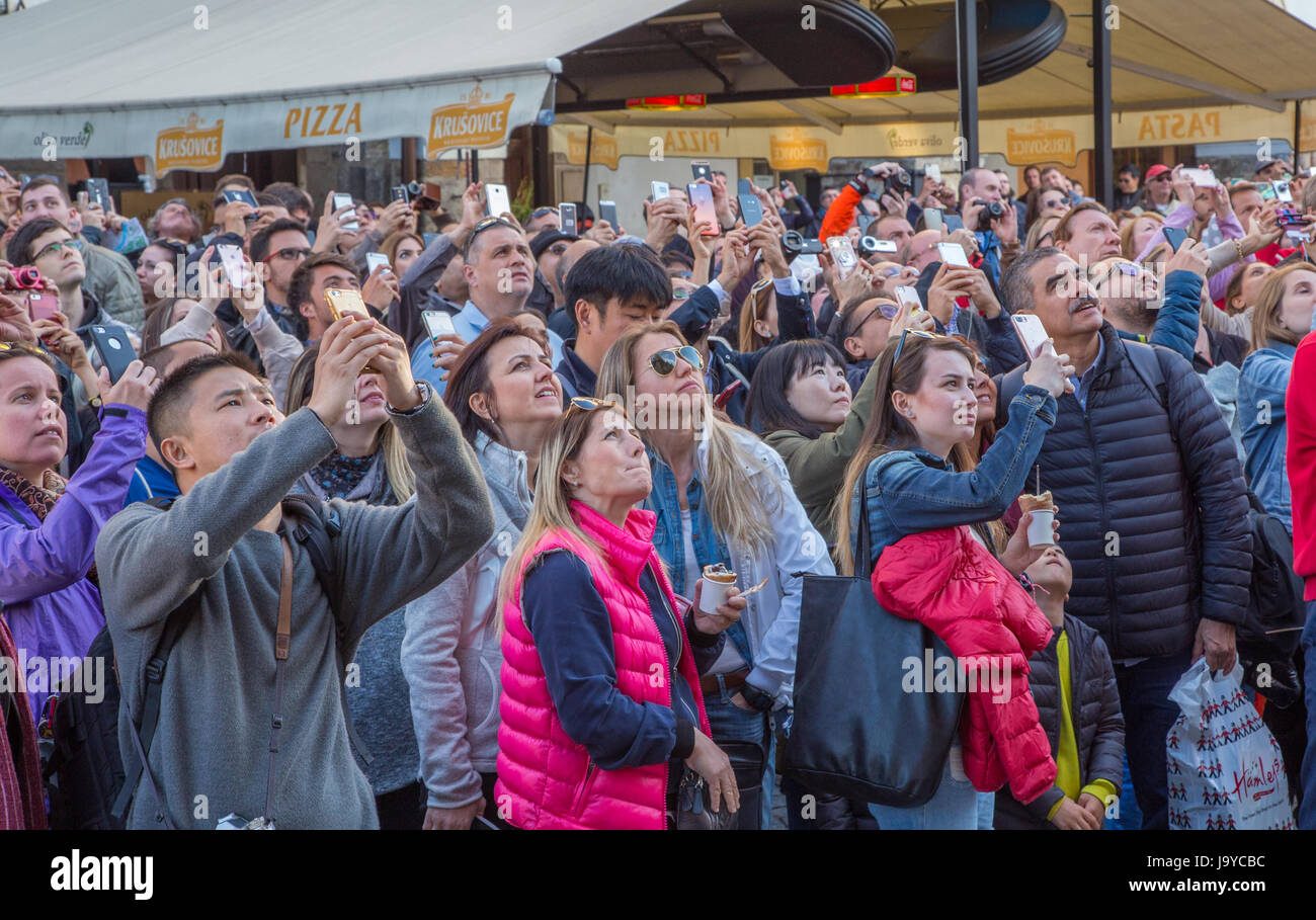 Crowd of people watching and filming on their smartphones - Stock Image