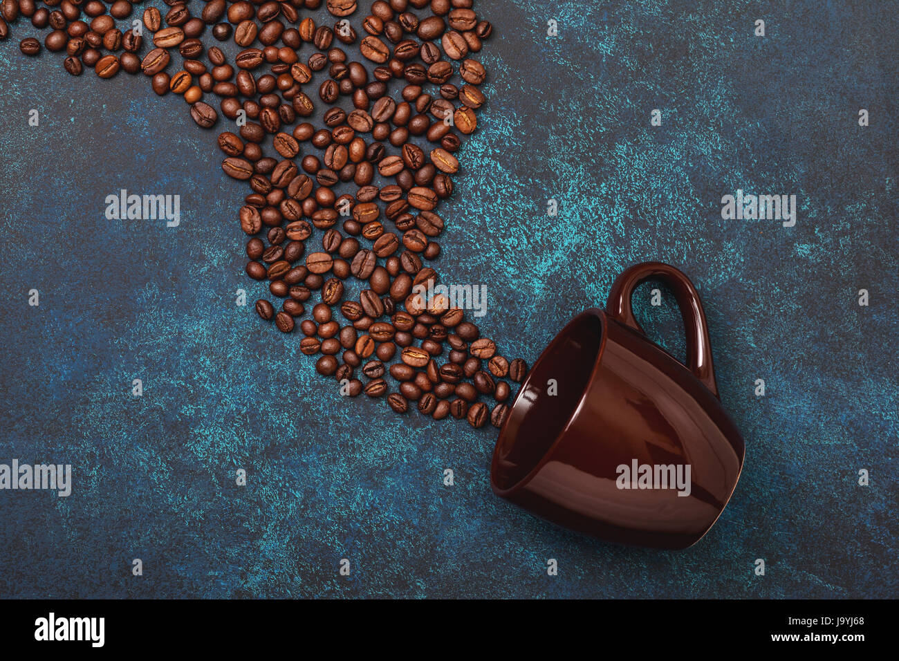 coffee beans and mug on blue concrete background. view from above - Stock Image