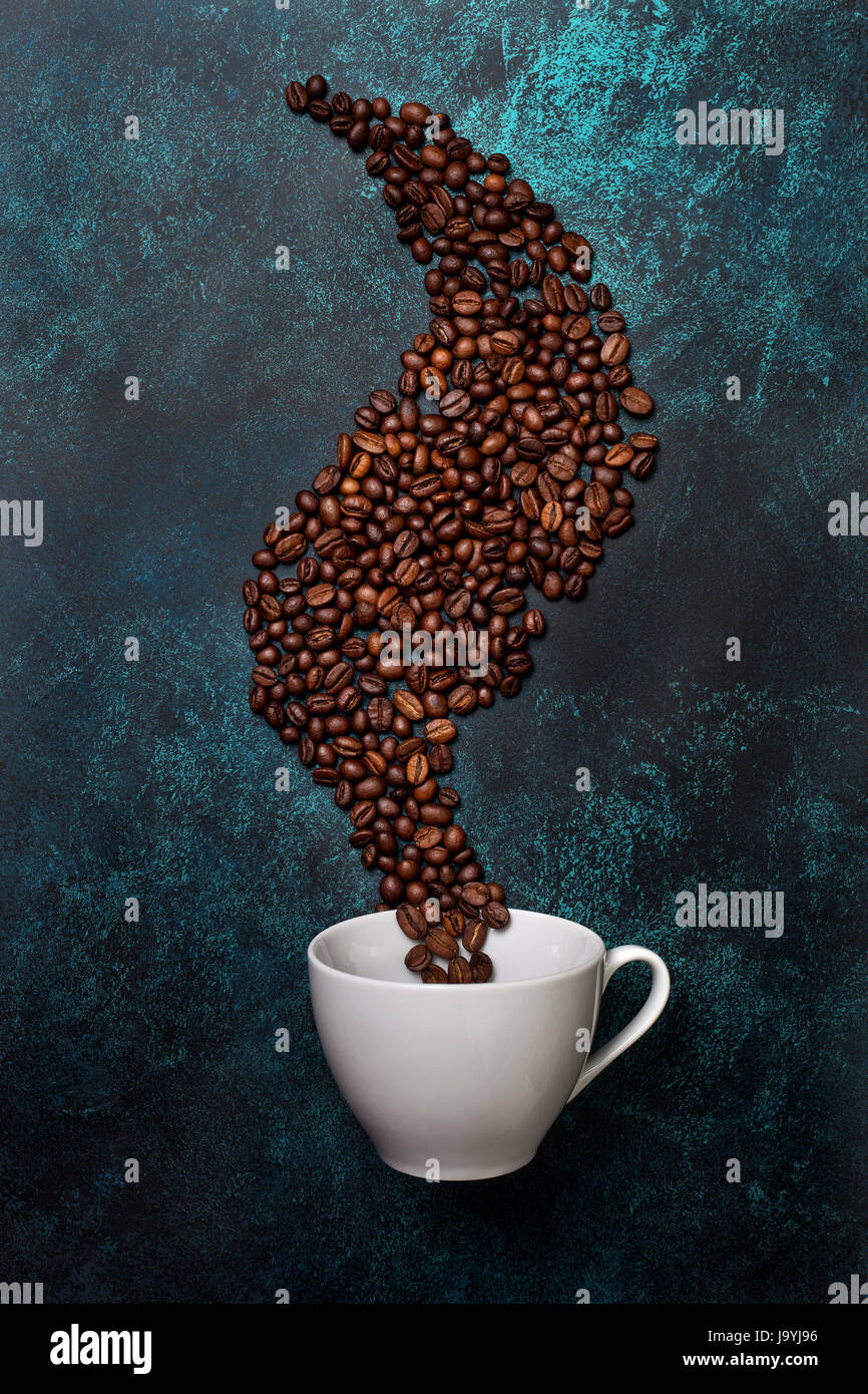 coffee beans and white mug on blue concrete background. view from above - Stock Image
