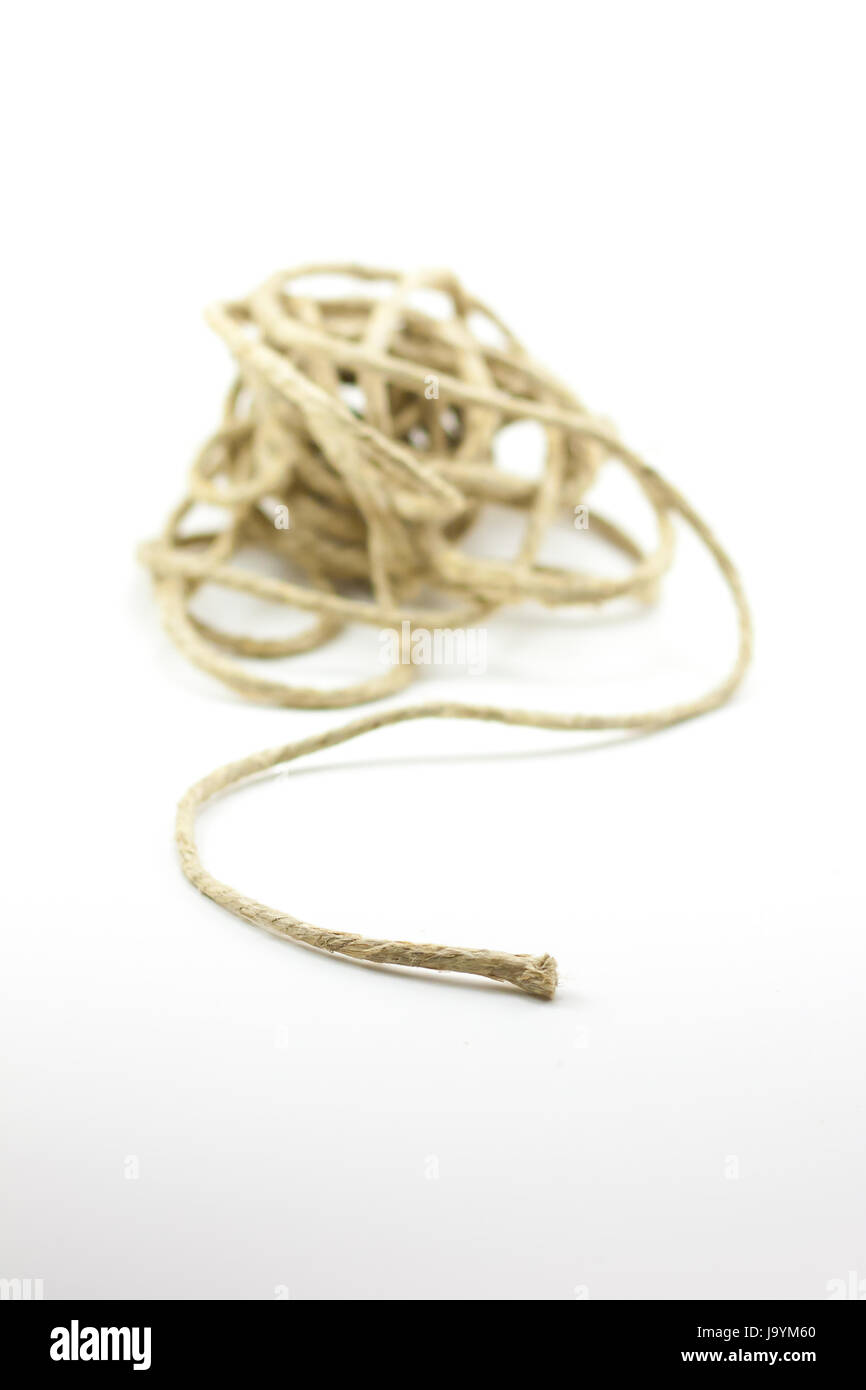 Tangled pile of twine with a single piece leading out. - Stock Image
