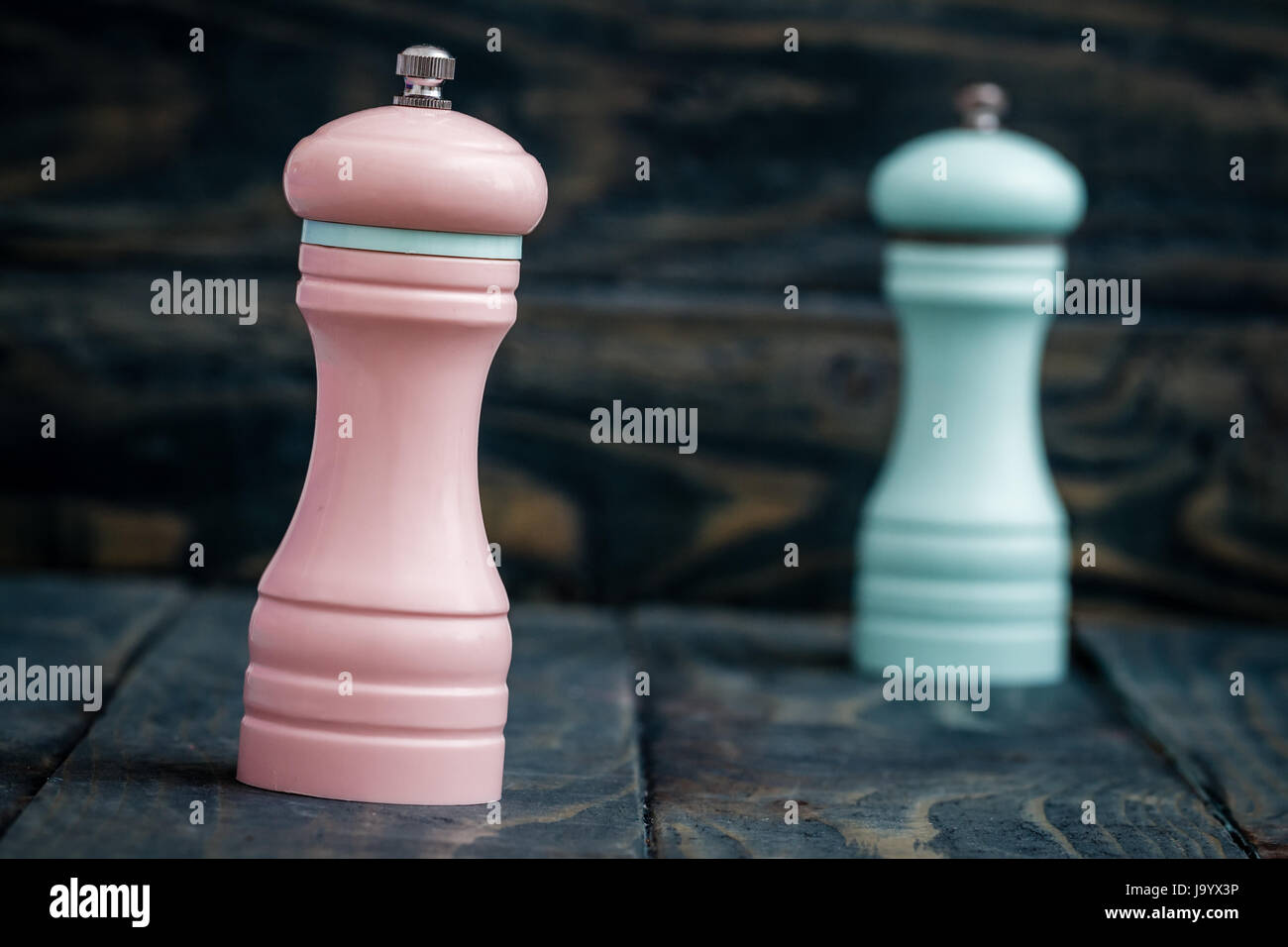 Pink and blue pepper mills on blue wooden background - Stock Image