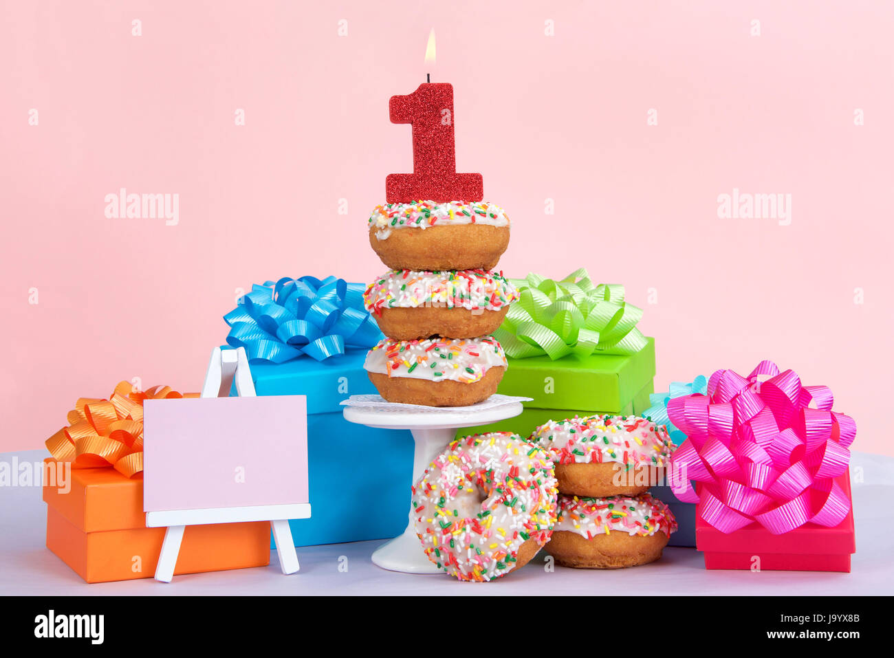 Cake Donuts With White Frosting And Colorful Sprinkles Stacked On Around A Small Pedestal Surrounded By Birthday Presents Number 1 Candle Burning