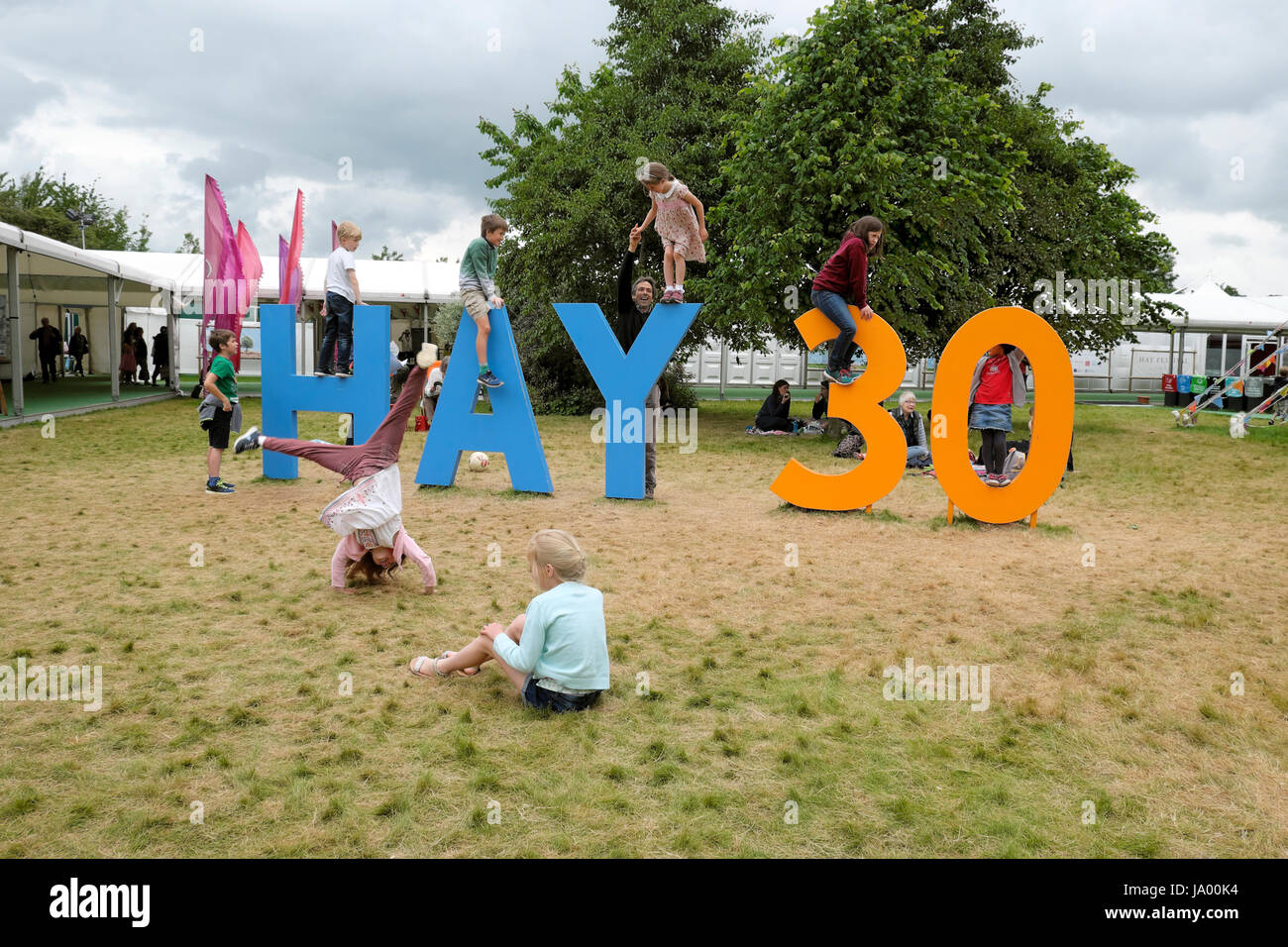 Kids playing outside climbing on the Hay 30 sign celebrating the 30th year of the Hay Festival, Hay-on-Wye, Wales - Stock Image