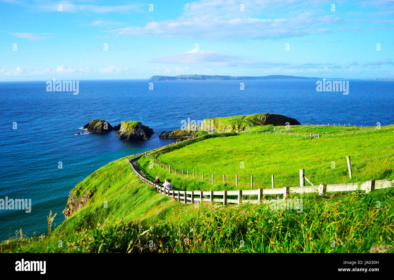 People Walking Along the Coastline Footpath to Carrick-a-Rede Rope Bridge in a Sunny Day, Giant's Causeway, - Stock Image