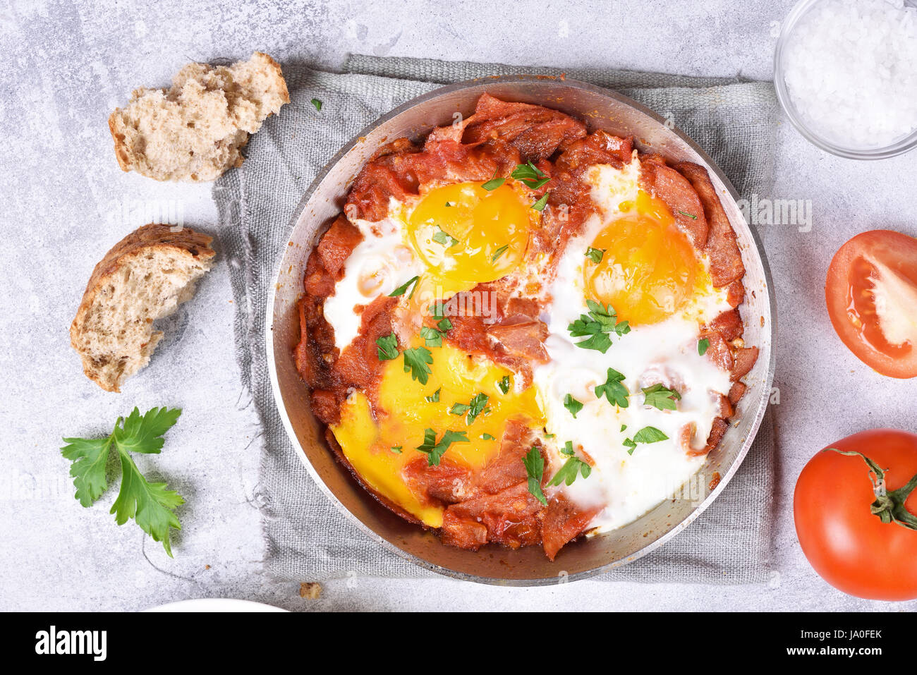 Fried eggs with bacon in frying pan, top view, close up - Stock Image