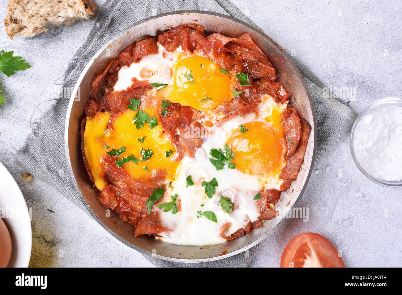 Fried eggs with tomato sauce and bacon in frying pan, top view, close up - Stock Image