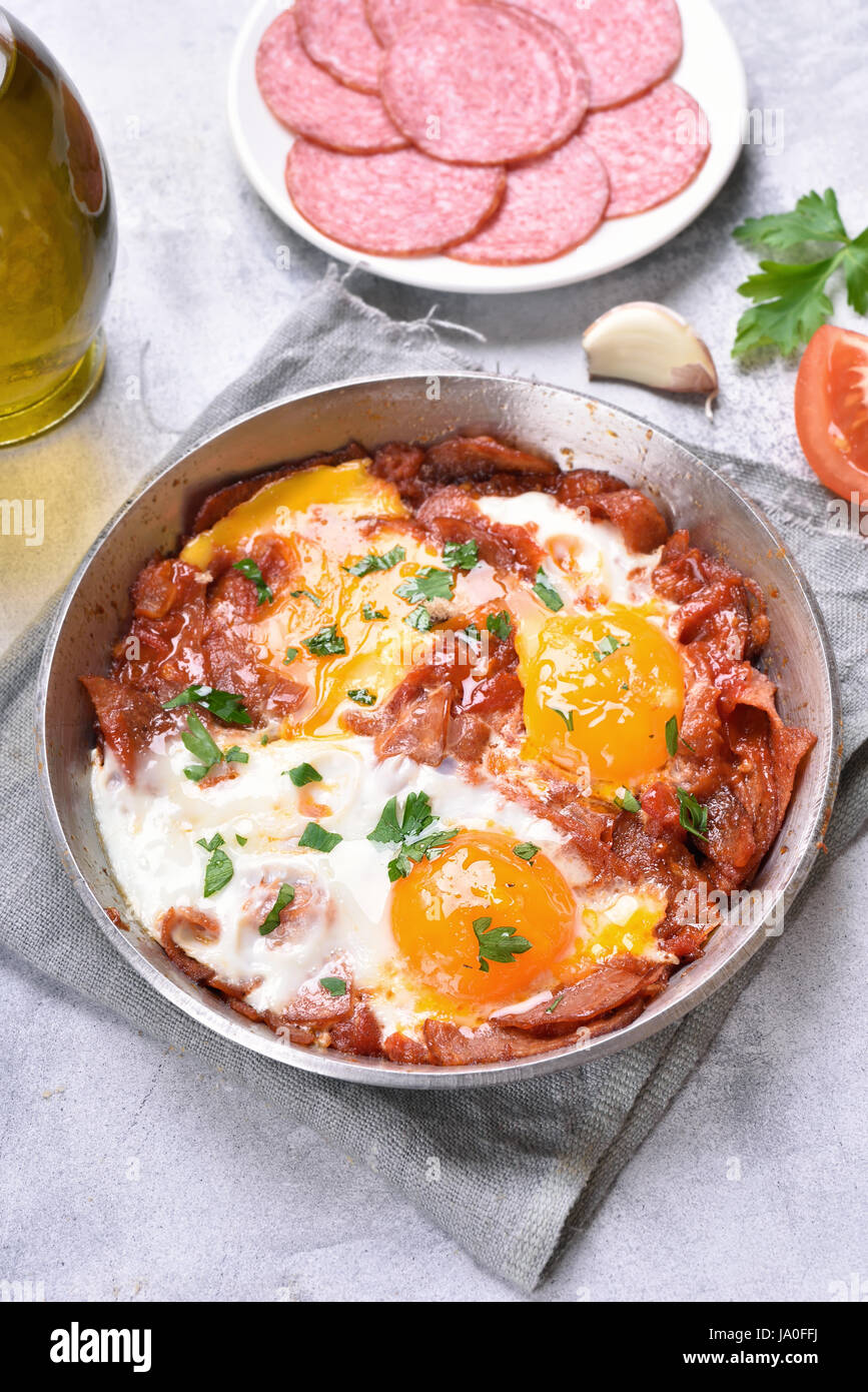 Breakfast with fried eggs and bacon in frying pan - Stock Image