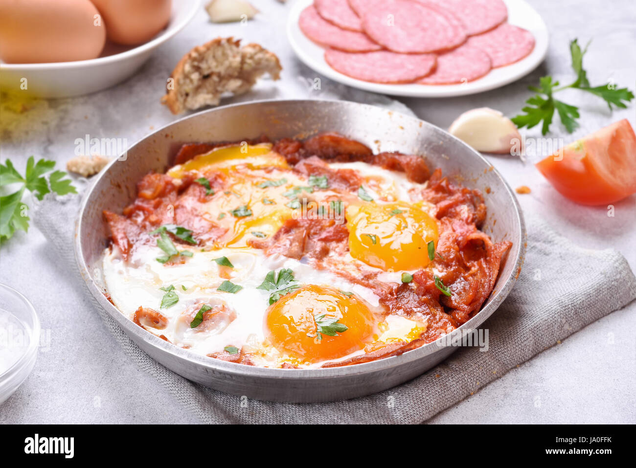 Morning food. Fried eggs with tomatoes and bacon in frying pan - Stock Image