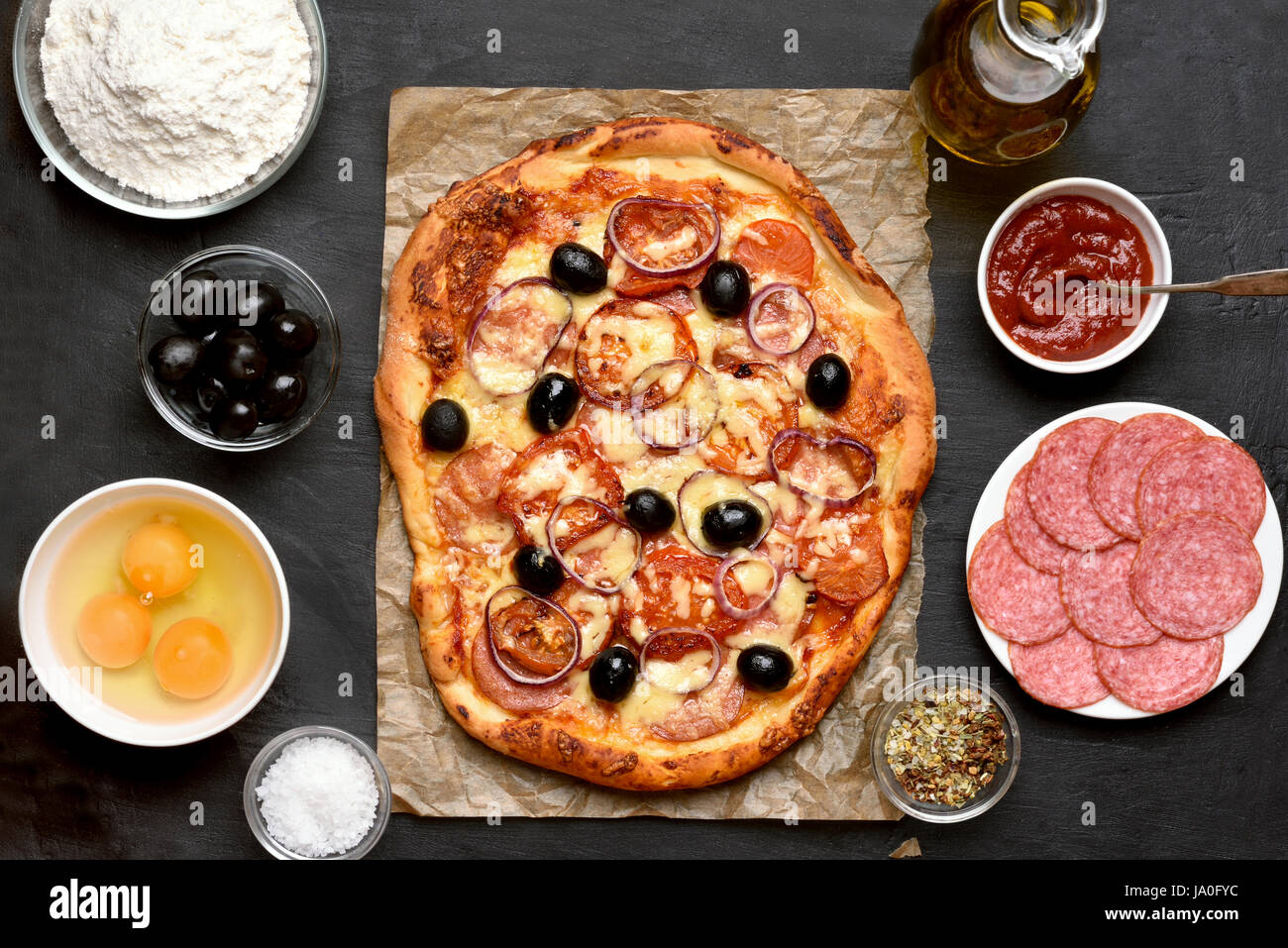Pizza and ingredients on dark background, top view - Stock Image