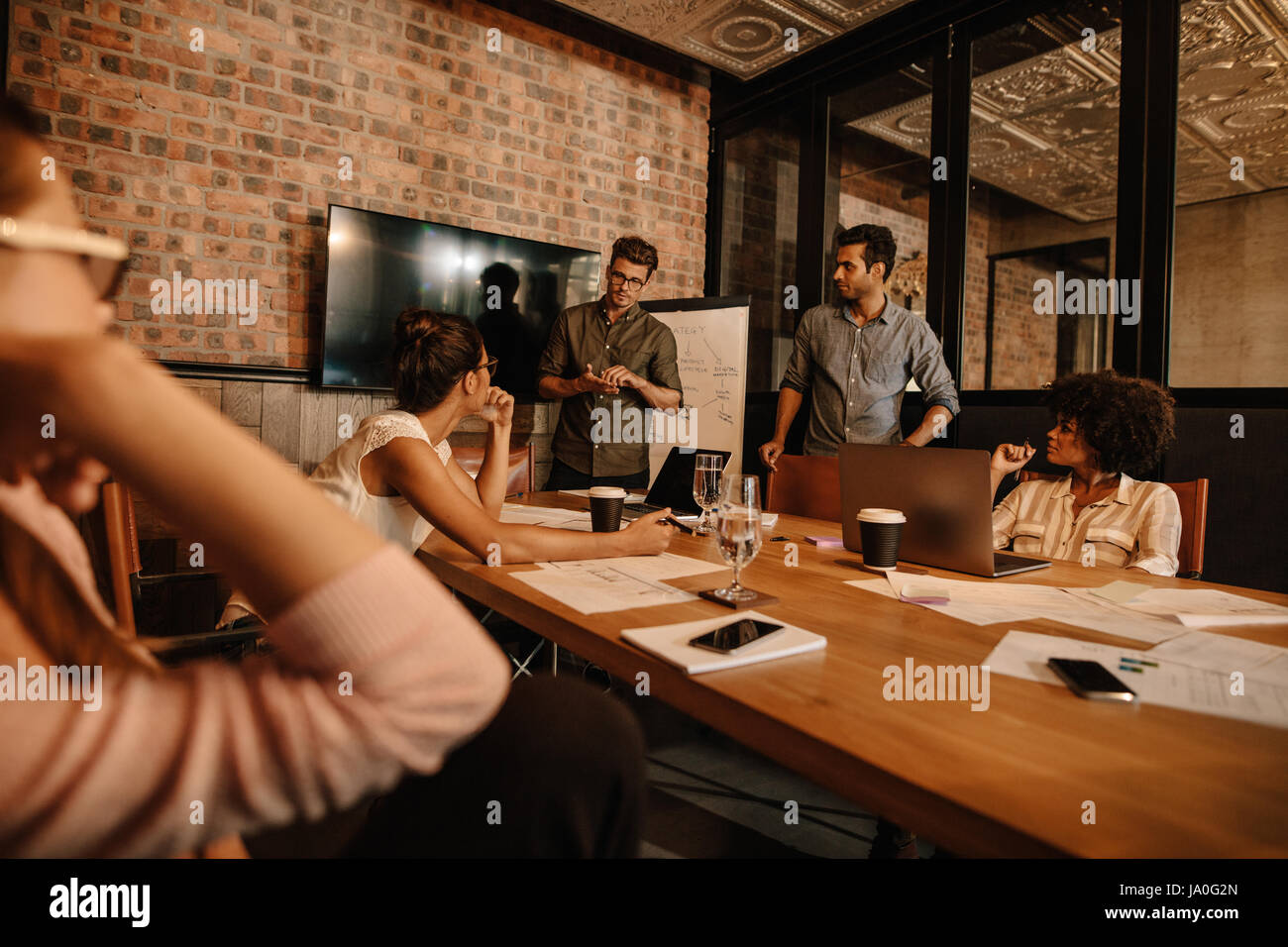 Creative team sitting around a table discussing new project plans. Mixed race people meeting in office. - Stock Image