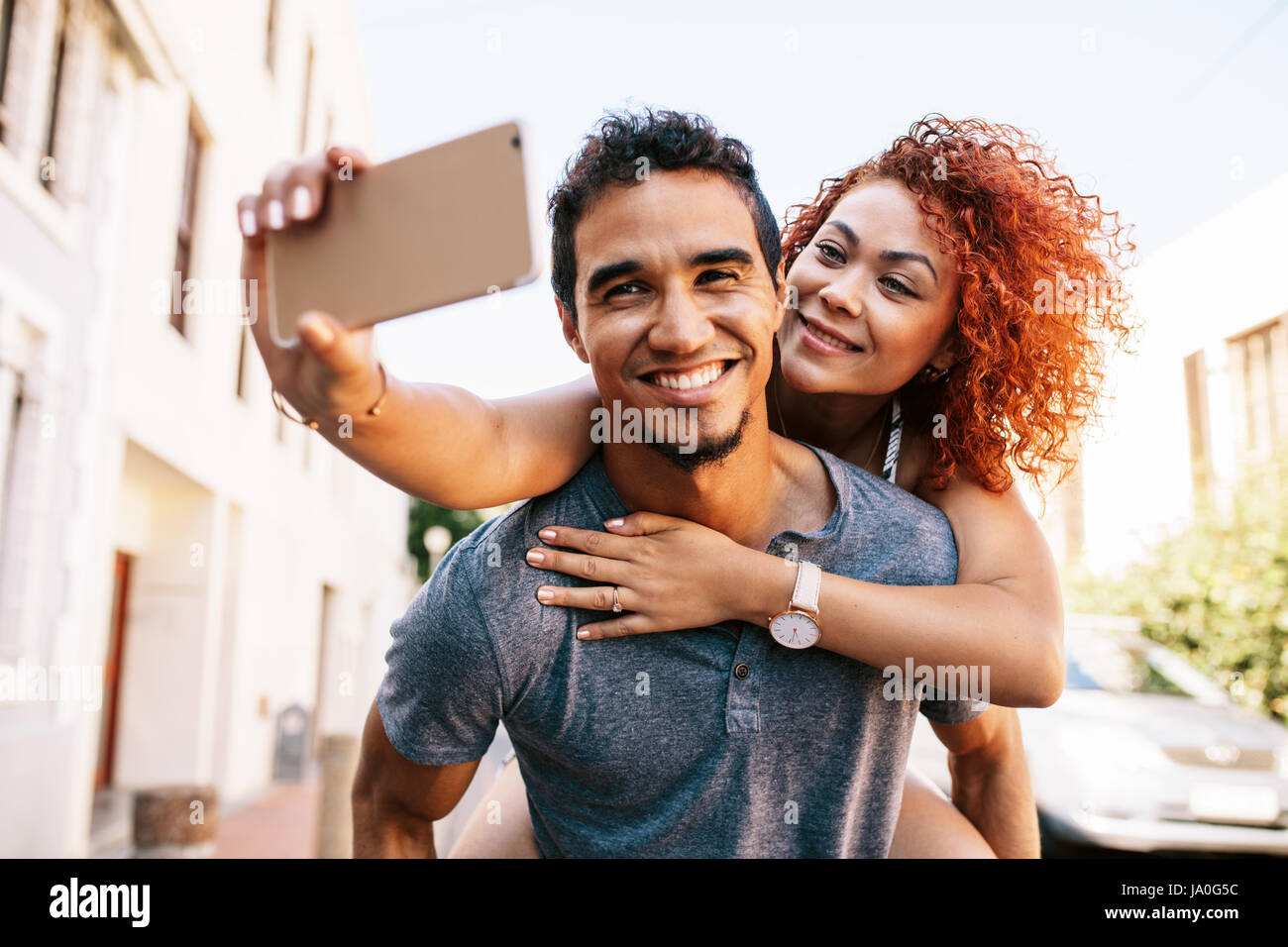 Smiling young woman riding piggy back on her partner while taking a selfie with her smartphone. Young man carrying - Stock Image