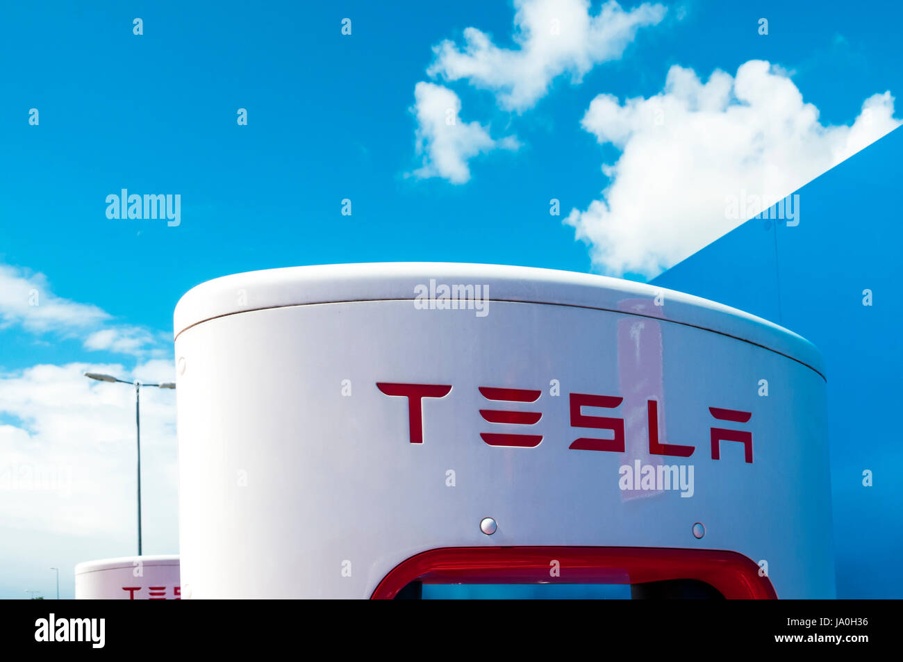 Electric car re-charging point for Tesla electric cars showing the Tesla name and logo - Stock Image