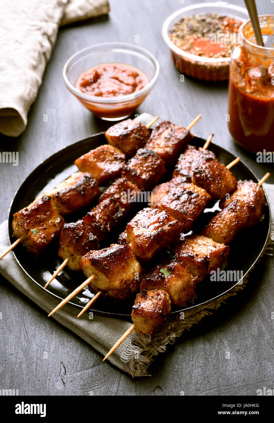 Grilled pork skewers on plate over dark stone background - Stock Image