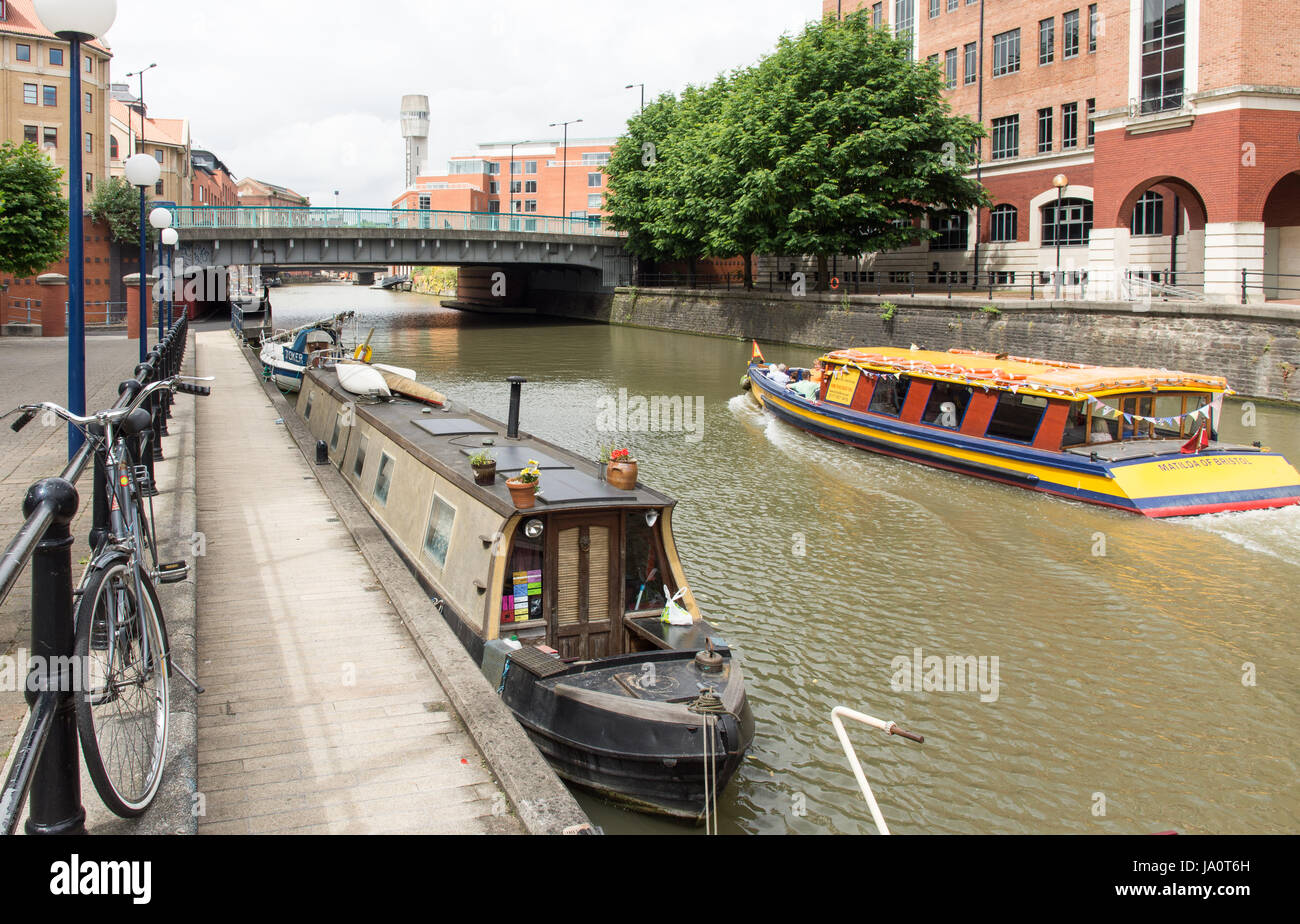 Bristol, England - July 17, 2016: A city ferryboat passes office buildings and narrowboats on Temple Quay in Bristol's - Stock Image