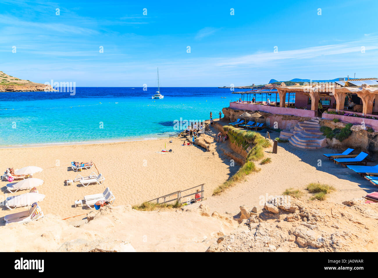 CALA COMTE BEACH, IBIZA ISLAND - MAY 17, 2017: view of sandy Cala Comte beach and restaurant building on shore, - Stock Image