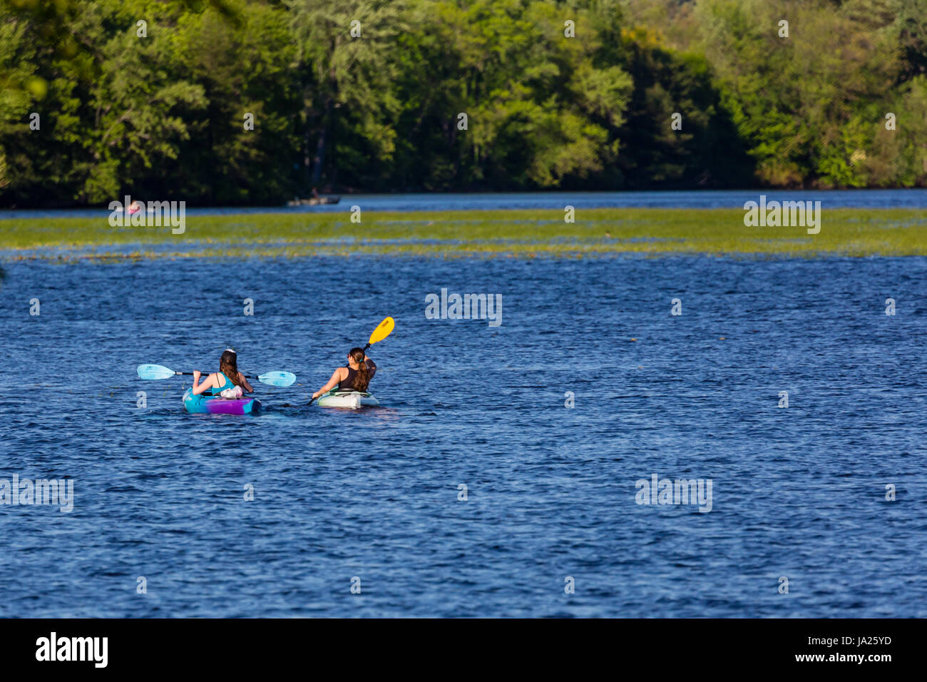 Two young women paddling kayaks across a lake in Wisconsin - Stock Image