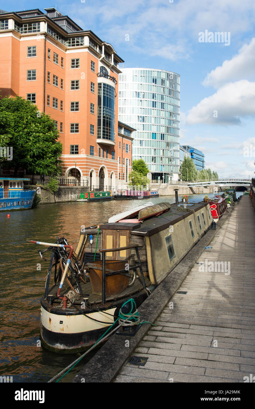 Bristol, England - July 17, 2016: Traditional narrowboats docked alongside modern office buildings on Temple Quay - Stock Image
