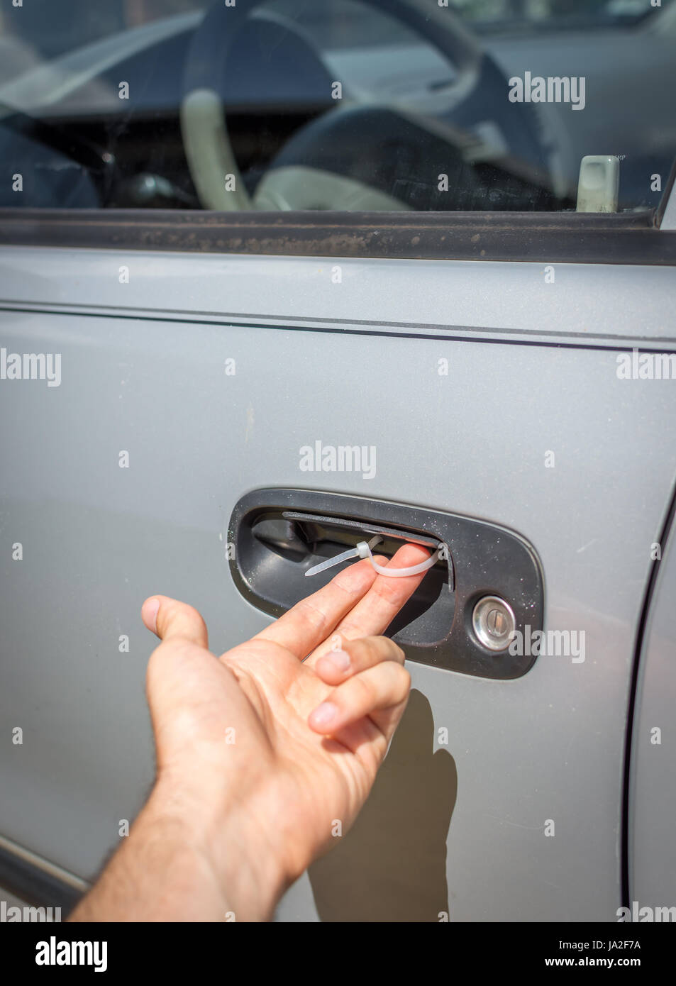 A makeshift car door handle fix using a simple zip tie looped through drilled holes. - Stock Image
