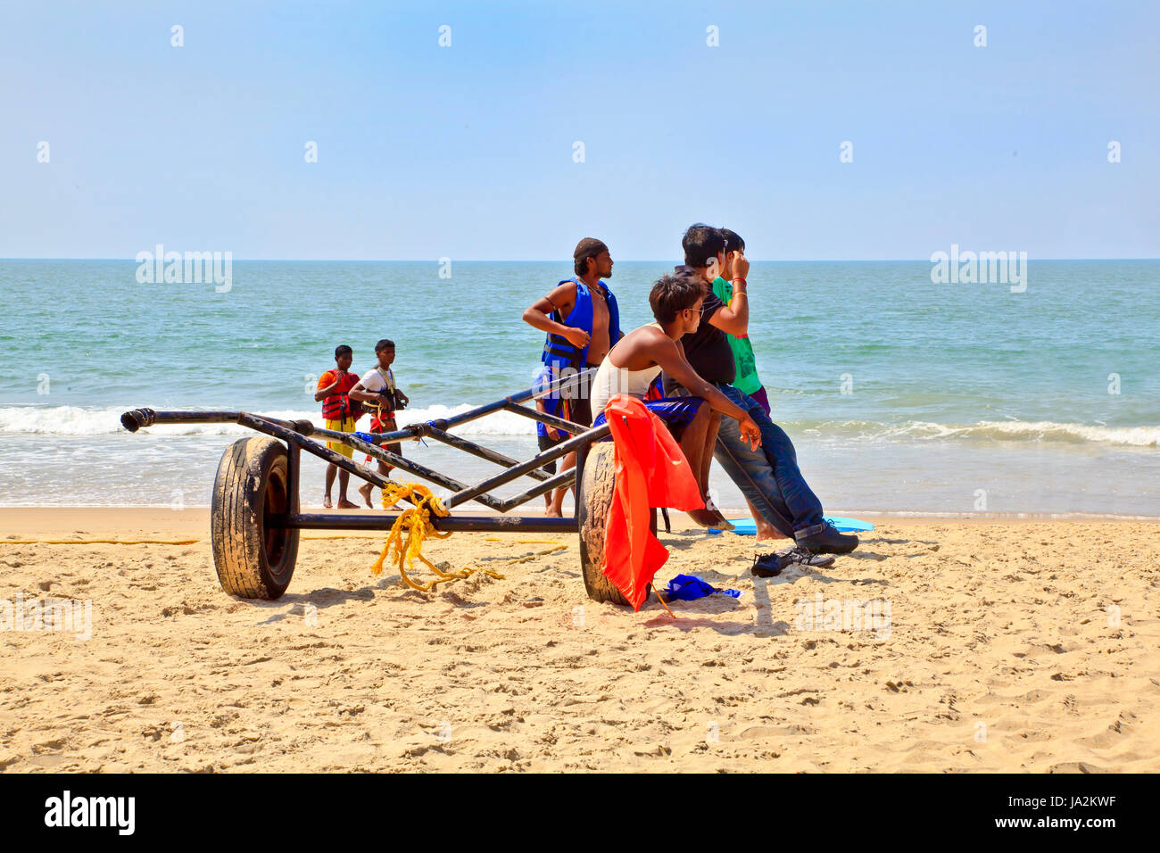 Goa, India - January 27, 2013: Horizontal Beach tropical landscape of paragliding sales assistants sat on a trailer Stock Photo