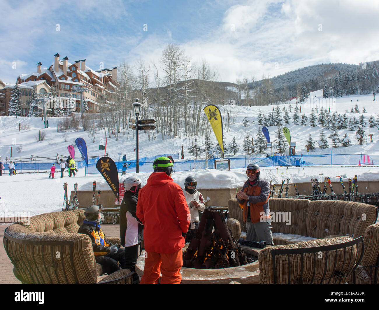 Skiers take a break around an outdoor fire at Beaver Creek, a ski resort near Avon, Colorado. - Stock Image