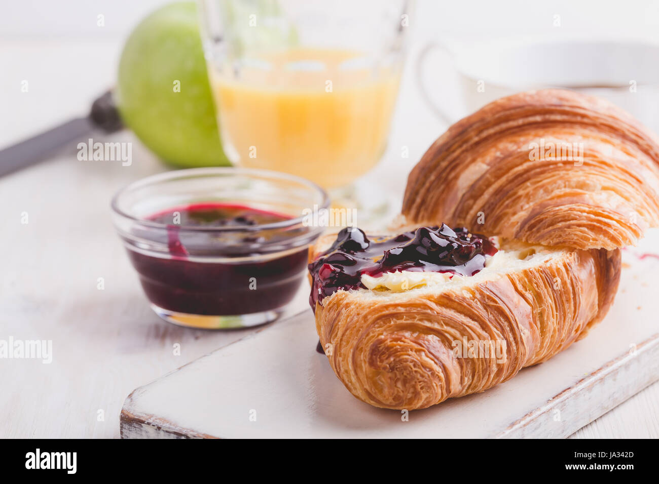 Breakfast on white wooden background - croissant, jam,  orange juice and coffee - Stock Image