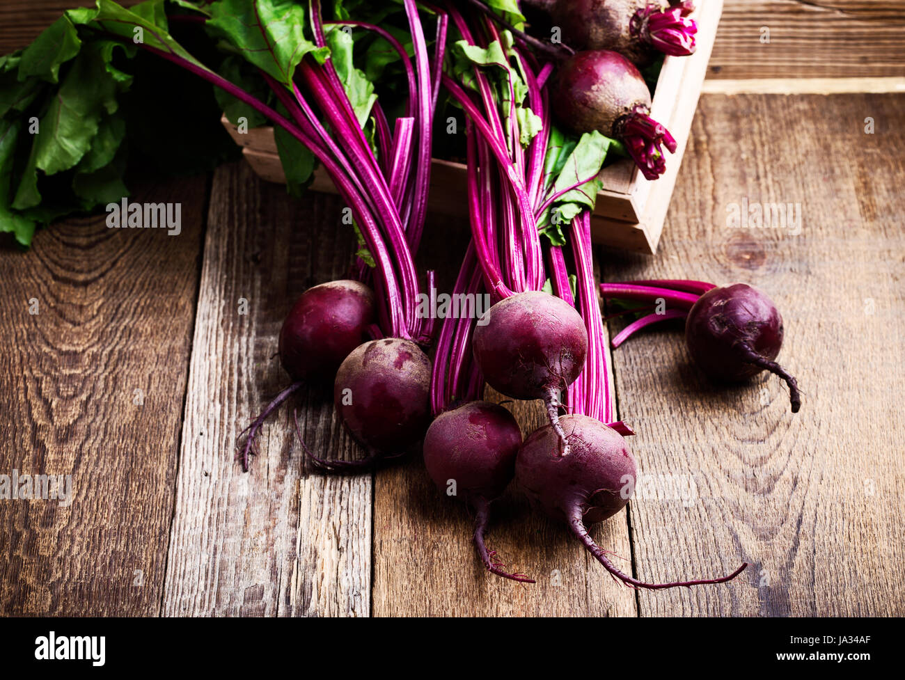 Organic  farm. Fresh beetroot in crate, vegetables on rustic wooden background - Stock Image