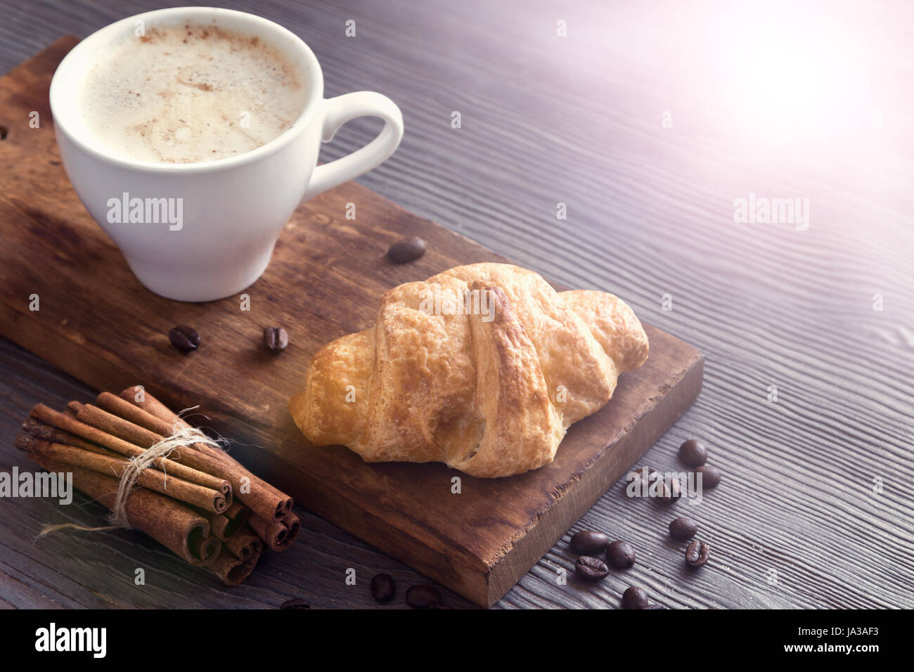 Coffee with croissant for breakfast. French croissant and Cappuccino coffee, tint image. - Stock Image