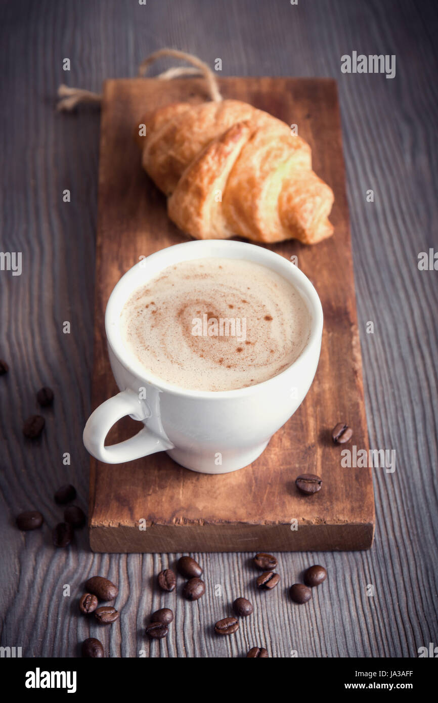 Coffee with croissant for breakfast. Cappuccino coffee and french croissant, tint image. - Stock Image