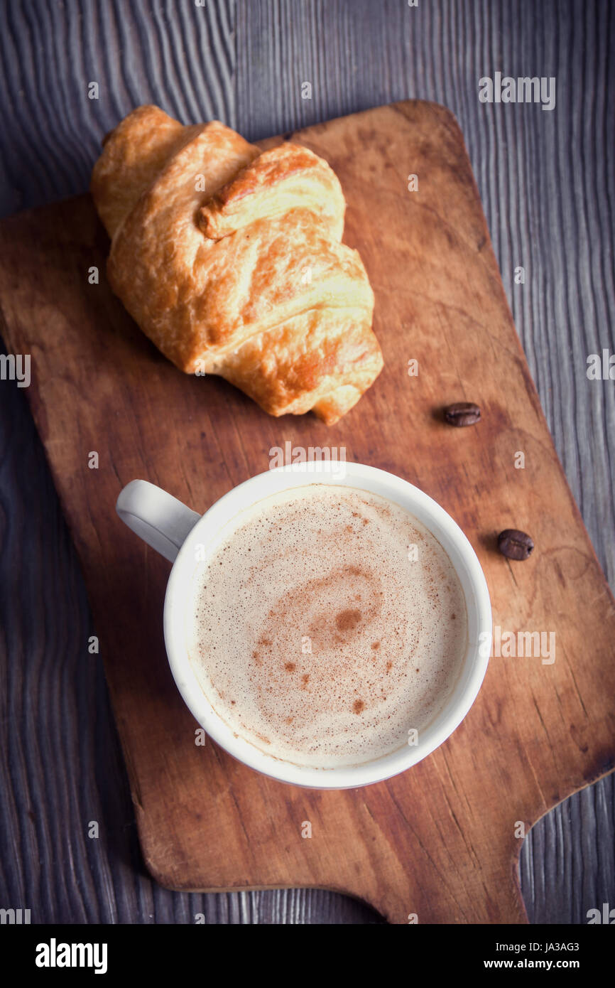 Coffee with croissant for breakfast. Cappuccino coffee, tint image with copy space. - Stock Image