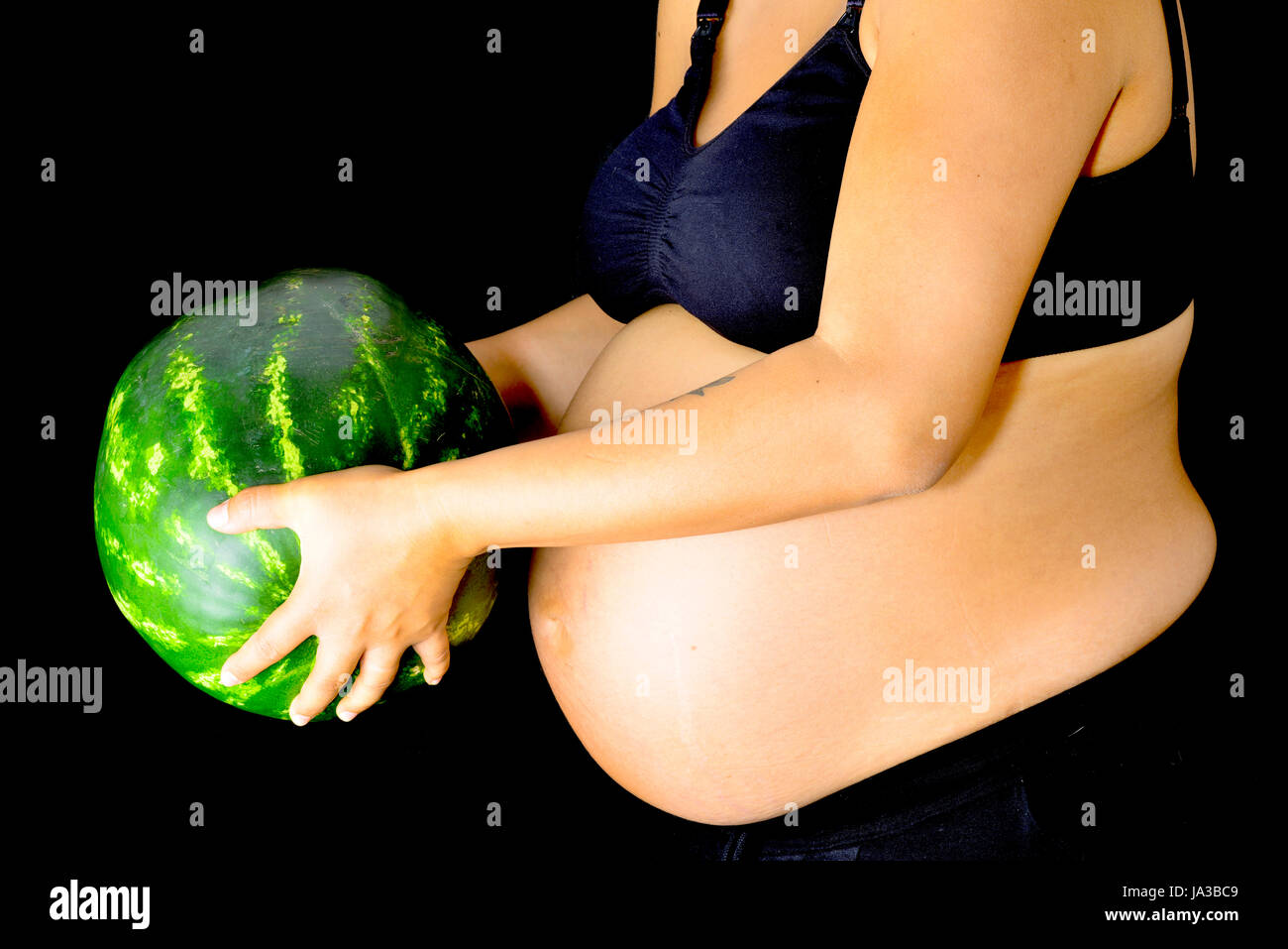 A pregnant woman holding out a huge watermelon in front of her abdomen. Stock Photo