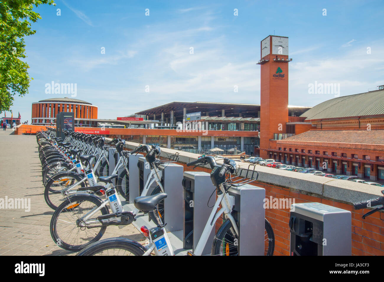 BiciMad bike parking and Puerta de Atocha Railway Station. Atocha street, Madrid, Spain. - Stock Image