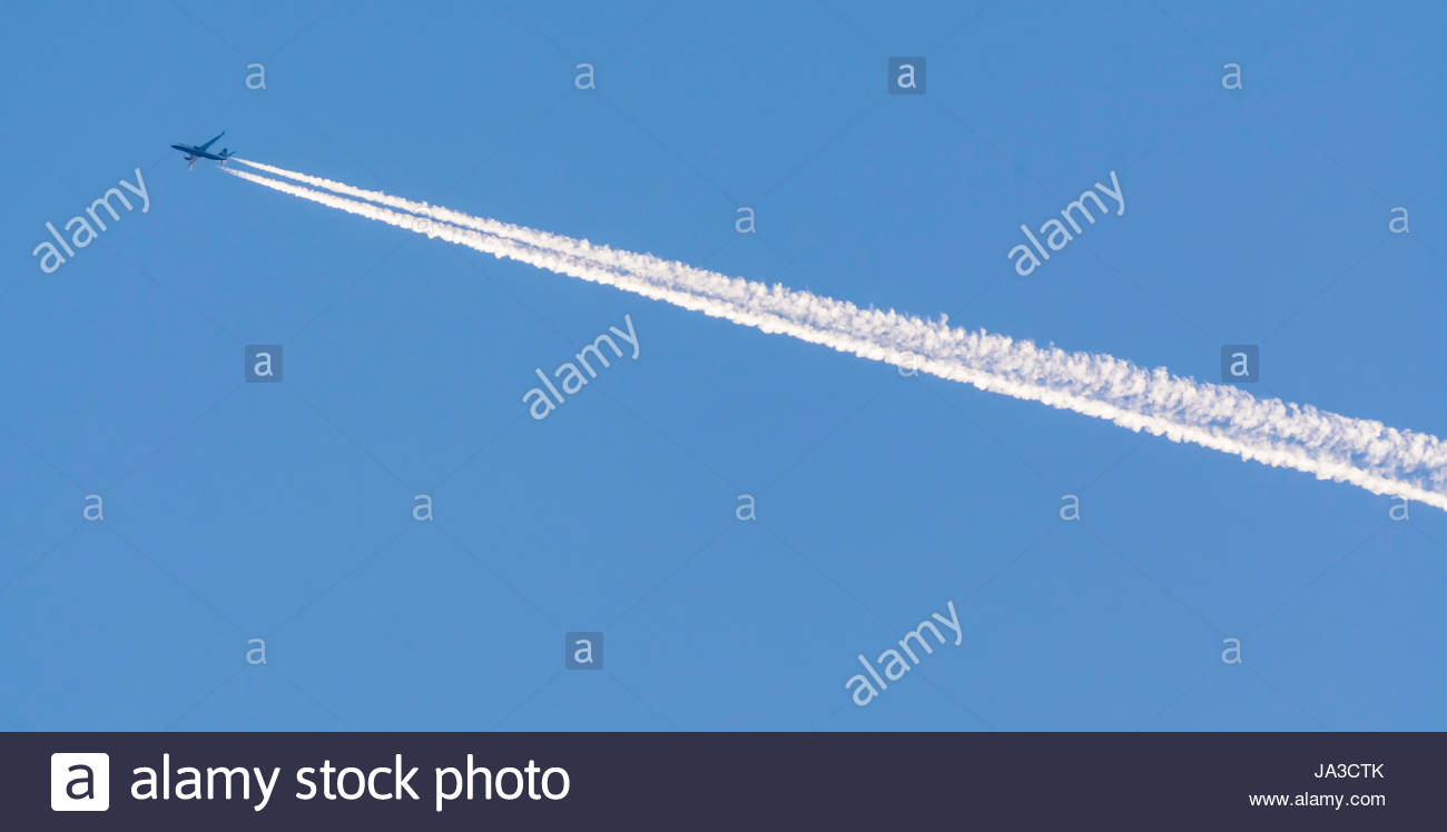 Condensation trails from a jet plane flying high in the sky against blue sky. - Stock Image