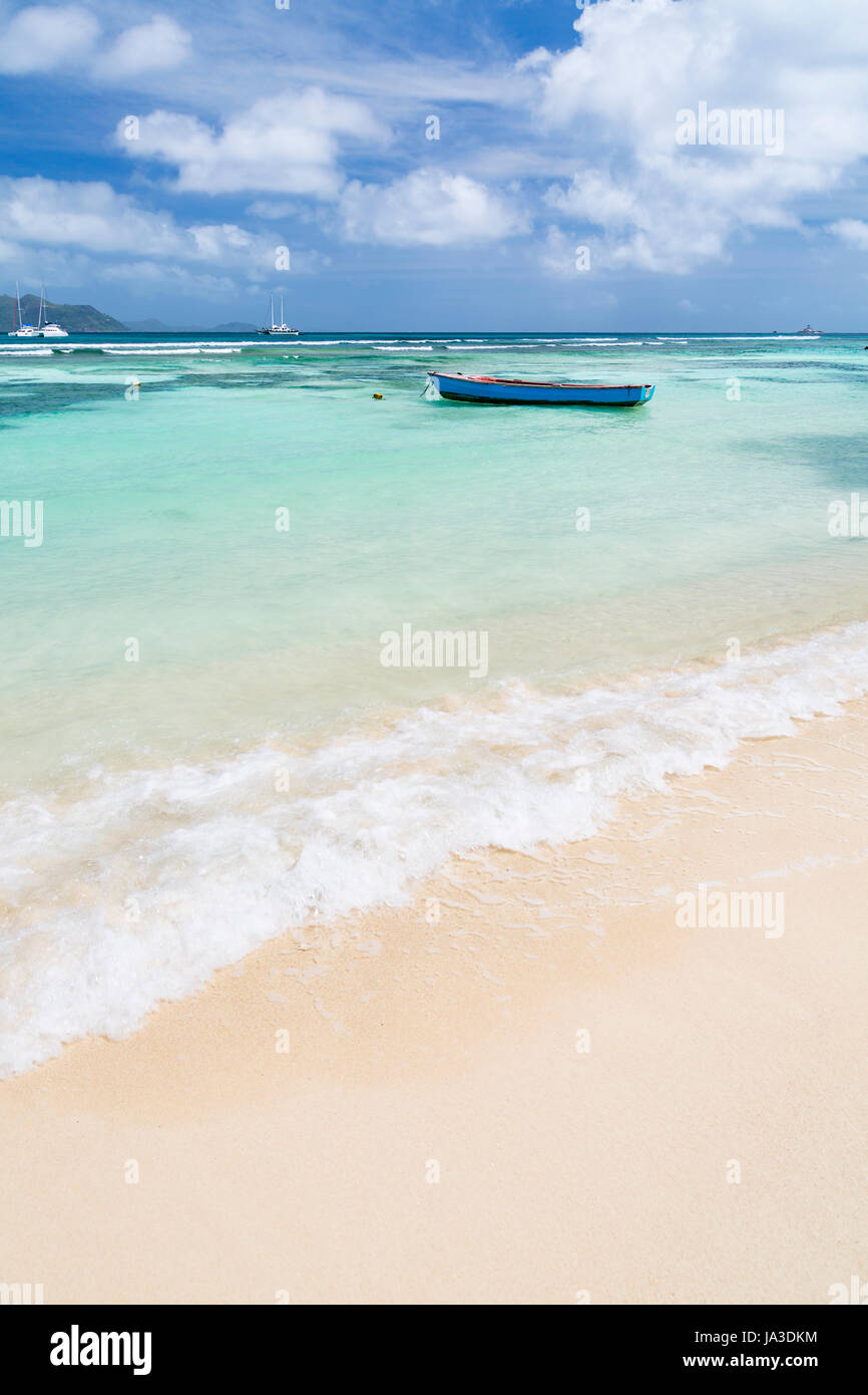 A little blue boat in a lagoon in La Digue, Seychelles with view to Praslin - Stock Image