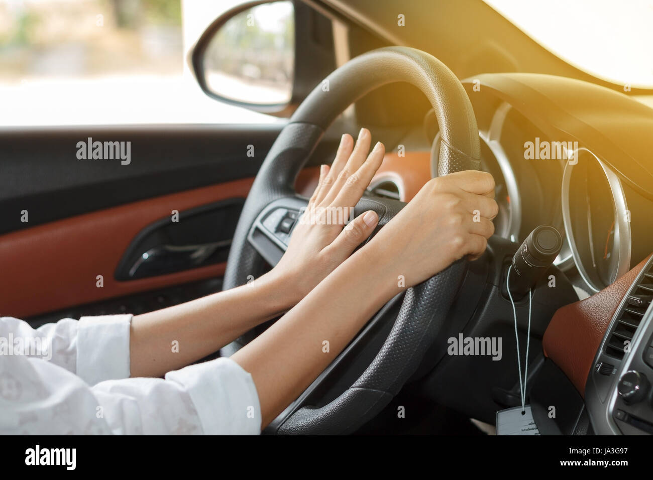 Asian women are driving cars on the road and squeeze klaxon.soft focus - Stock Image