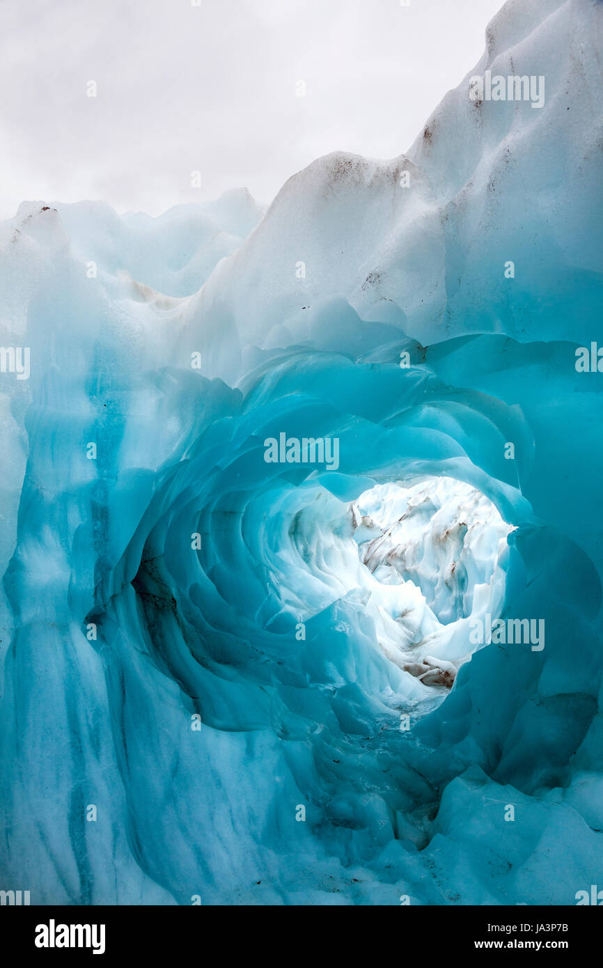 Ice arch or hole in the surface of a glacier, Fox Glacier, South Island, New Zealand - Stock Image