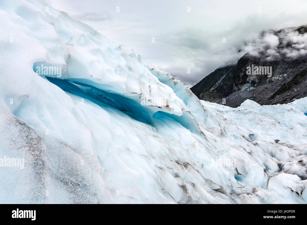Blue horizontal fissure crevasse in the ice of a glacier, Fox Glacier, New Zealand - Stock Image