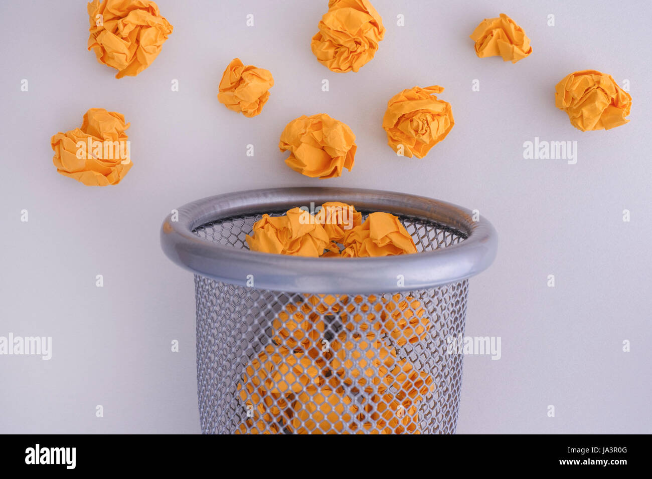 Yellow crumpled paper balls rolling out of a trash can. Idea Concept. - Stock Image