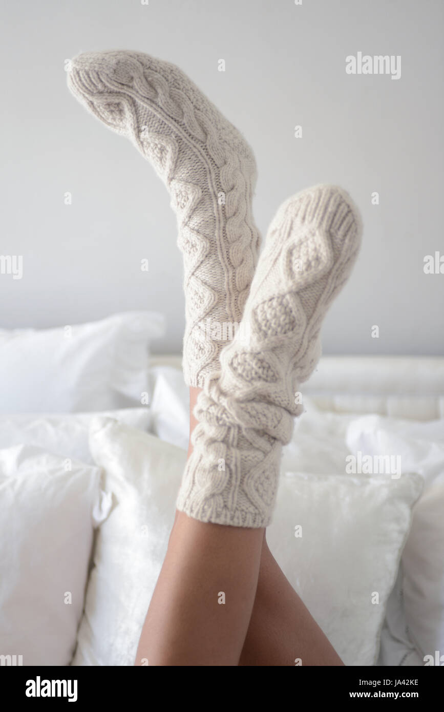 Pair of female legs wearing cosy cream socks lying on bed with feet in air with white pillows behind - Stock Image